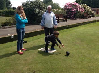 Young visitor to Brentwood Bowling Club open day 2014 develops his delivery technique, watched by his mum and club president Byron Davies.