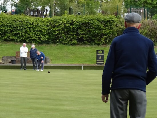 An  official checks one of the rinks as volunteer Trevor Pedley delivers a wood at Brentwood Bowling Club.