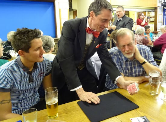 Keith Howson assists one of the close-up magicians with a card trick.
